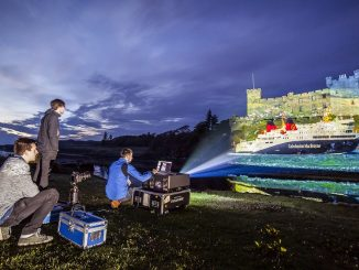 A large projector on a grass verge at the side of a loch surrounding Dunvegan Castle, clouds are moving overhead as the sun sets. Behind the projector a man is crouched using a laptop.The machine is projecting a beam of light across the water which is projecting the image of a Caledonian Macbrayen Ferry on to the side of the castle. Another man is crouched behind a camera and slider aparatus while a third man stands to the left of the projector looking towards the castle.